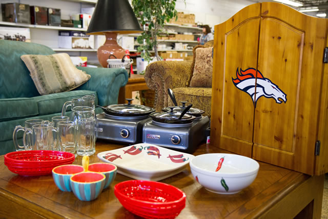 table with party supplies, bowls, warmers, broncos dart board, etc