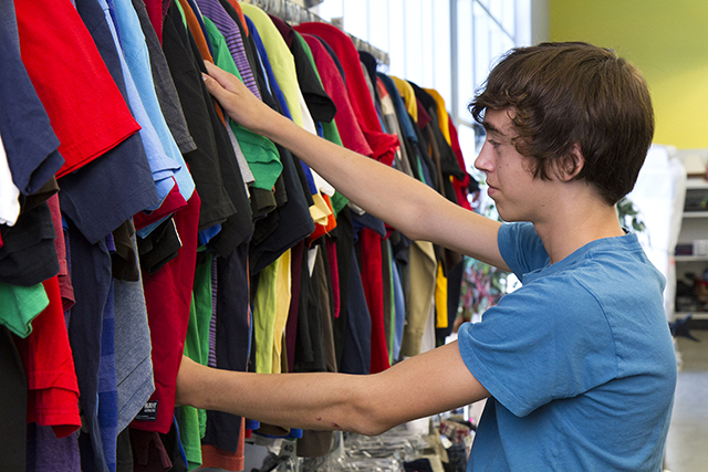 student sorting through a rack of shirts