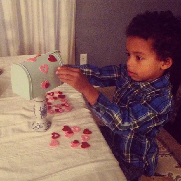 boy decorating valentine mailbox