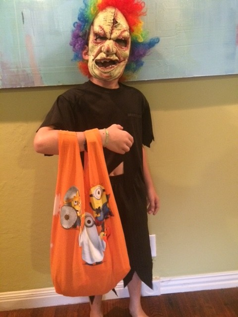boy in scary clown  costume with bag